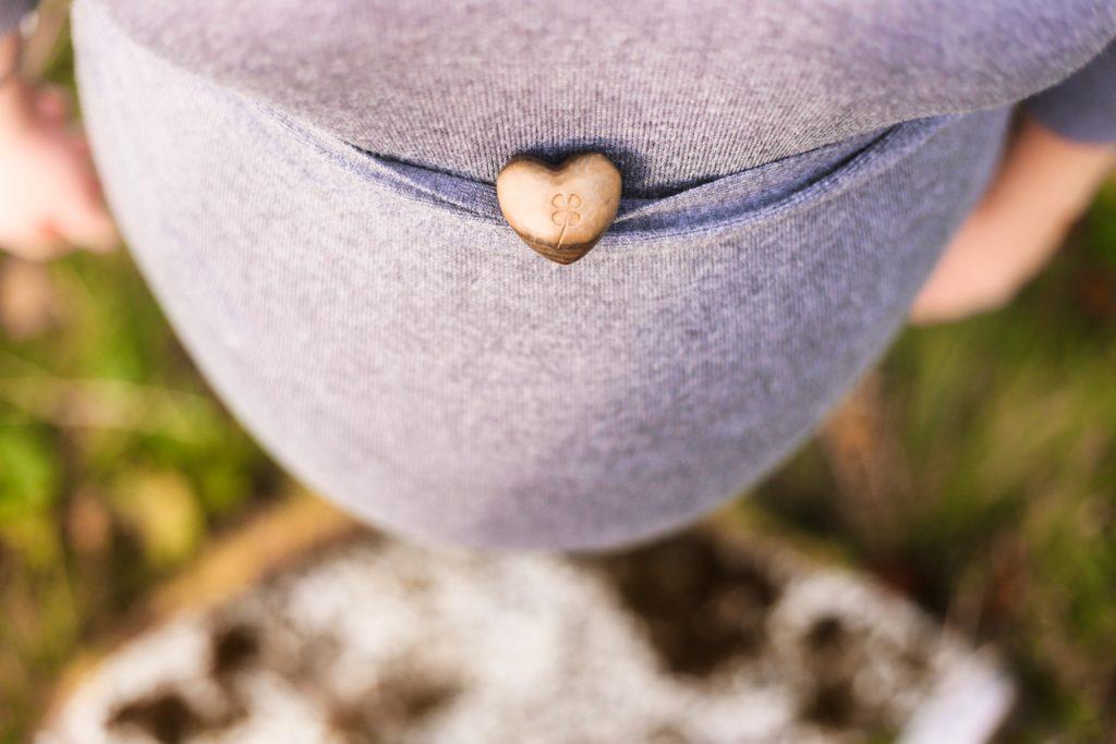 Ansicht eines runden Babybauches von Oben auf dem ein kleiner herzförmiger Stein liegt