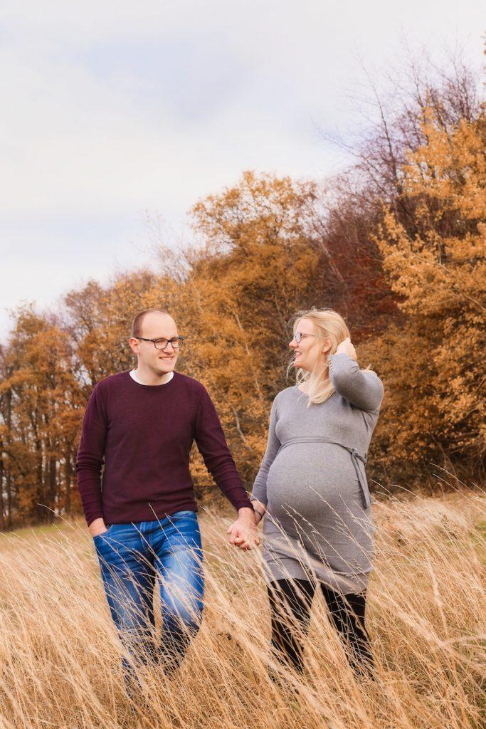 Ein Mann und schwangere Frau laufen lächelnd Hand in Hand über eine herbstliche Wiese