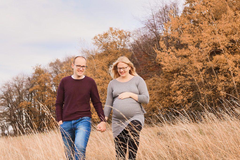 Mann und schwangere Frau laufen lächelnd über eine Wiese