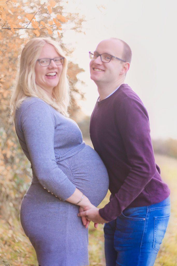 Ein Mann sieht den Bauch ein während im seine schwangere Frau mit rundem Bauch gegenüber steht