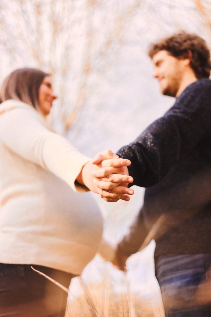 Mann und schwangere Frau halten Hände